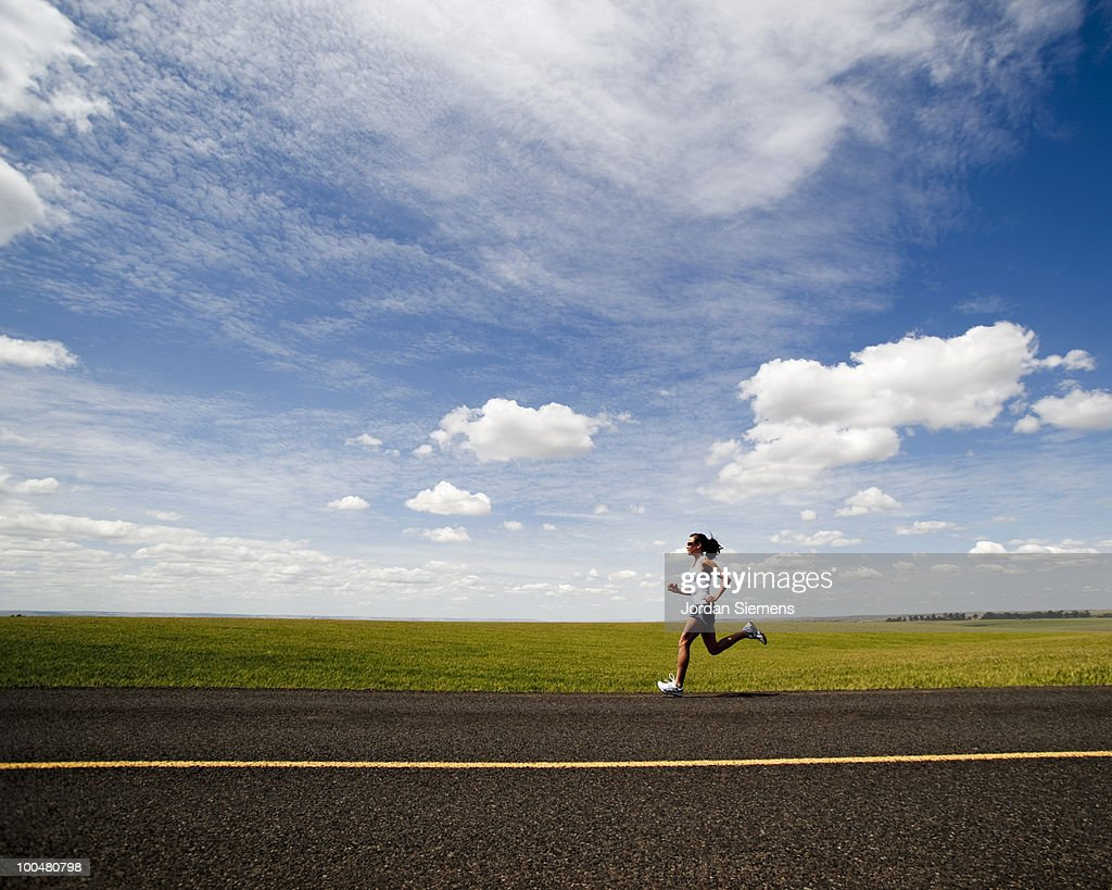 A fit woman running on a rural country road. : Stock Photo