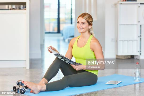 Fit woman siting on exercise mat with magazine