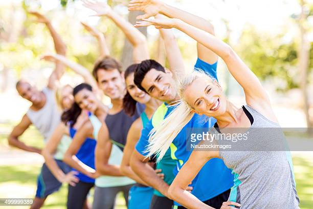 Fit Woman With Friends Exercising At Park