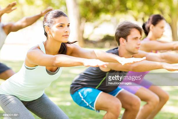 Fit Woman With Friends Practicing Squat Exercise In Bootcamp