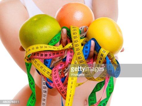 Fit femme avec mesure bandes de fruits frais.  Temps pour les régimes amincissant. : Photo