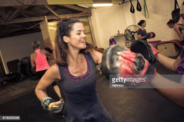 Fit women punching with her fitness trainer