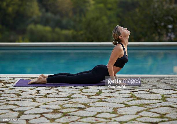 Fit yoga teacher making Bhujangasana (Cobra Pose)