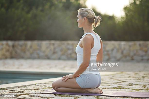 Fit yoga teacher making Virasana (Hero Pose)