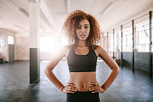Portrait of fit young african woman standing in gym with her hands on hips. Fitness model posing to camera.