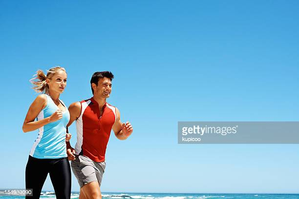 Fit young couple jogging on beach