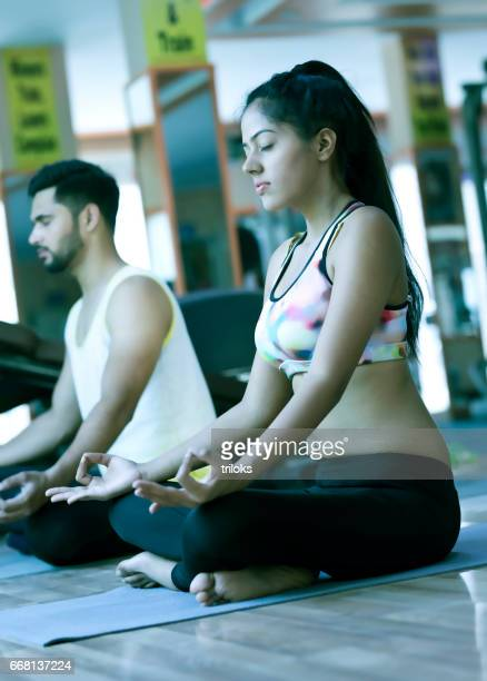 Fit young couple meditating