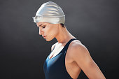 Side view of fit young female swimmer on black background. Fitness woman in swimming costume concentrating.