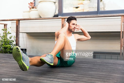 Fit young man doing crunches on floorboard