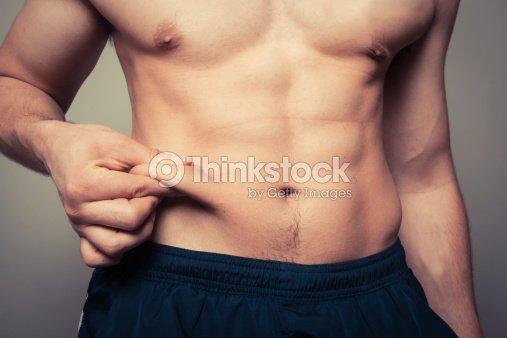 Fit young man Pellizcar su estómago : Foto de stock