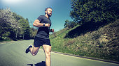 Fit young man in sportswear listening to music on earphones while running alone down a country road on a sunny day