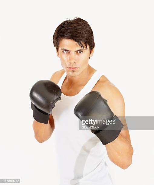 Fit young man wearing boxing gloves against white background
