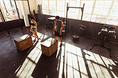 High angle view of man and woman about to jump on fit box at gym. Fit young people doing box jump in a cross training gym