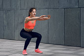 Fit young woman doing squats, strengthening her core, working out on a mat, lifestyle and health concept