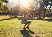 Full length outdoor shot of fit young woman exercising in park. She doing squatting on a sunny morning.