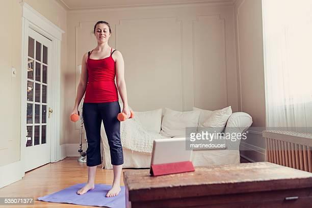 Fit jungen Frau Ausübung zu Hause mit digitalen tablet, horizontale.