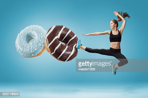 Fit young woman fighting off bad food on a blue : Stock Photo