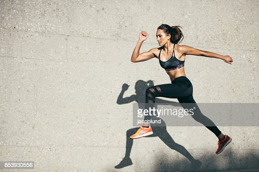 Fit young woman jumping and running : Stock Photo