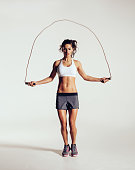 Fit young woman skipping rope. Portrait of muscular young woman exercising with jumping rope on grey white background.