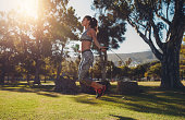 Full length portrait of fit young woman skipping with a jump rope in the park on a summer day.