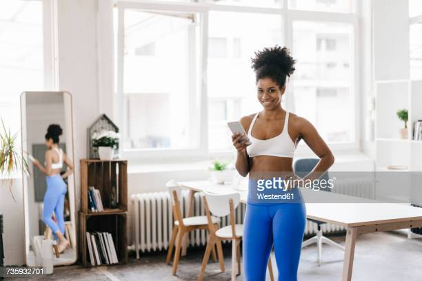 Fit young woman standing in her home office