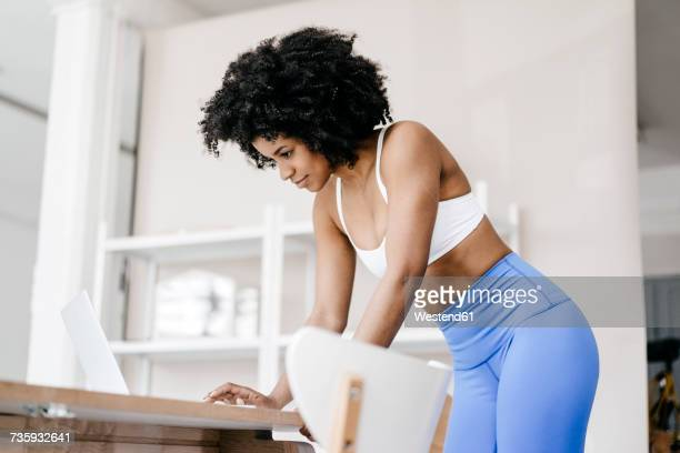 Fit young woman using laptop at home
