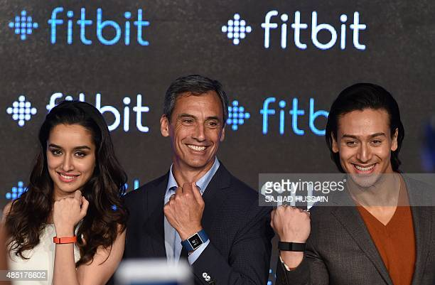 Fitbit's Chief Revenue Officer Woody Scal and Indian Bollywood actors Shraddha Kapoor and Tiger Shroff pose for a photograph during a promotional...
