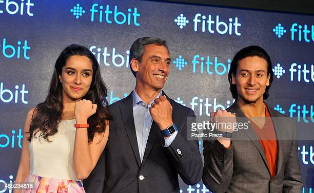 Fitbit's Chief Revenue Officer Woody Scal and Indian Bollywood actors Shraddha Kapoor and Tiger Shroff pose for a photograph during the promotional...