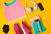 Fitness accessories on a yellow background. Sneakers, bottle of water, earphones and sport top. Still life