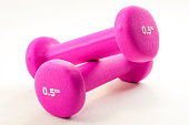 Fitness activity and the health benefits of exercising concept with light pink dumbbells isolated on white background with a clipping path included