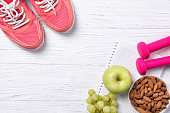 Fitness and healthy eating concept, pink sneakers and pink dumbbells with apple, grapes and almond nuts on notepad, wooden background, top view with copy space