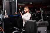 Fit man is  training legs on leg press machine in the gym.Sport training indoors. Sport concept, healthy lifestyle, gym concept.