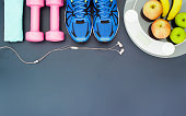 Fitness and weight loss concept, sport shoes, dumbbells, towel, earphone, weighting scale, apples, bananas, top view with copy space