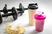 Fitness and workout concept with dumbbells, protein shakers  and a scoop in protein powder. The two shakers have black and pink lids and the background is white