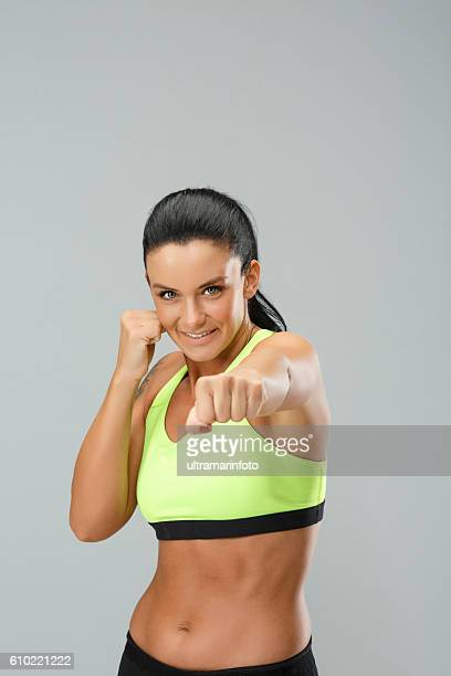 Fitness  Athletic young woman warms up before training   Female kickboxing