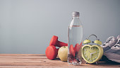 Fitness background with bottle of water, apple, dumbbells and sport shoes on wooden table