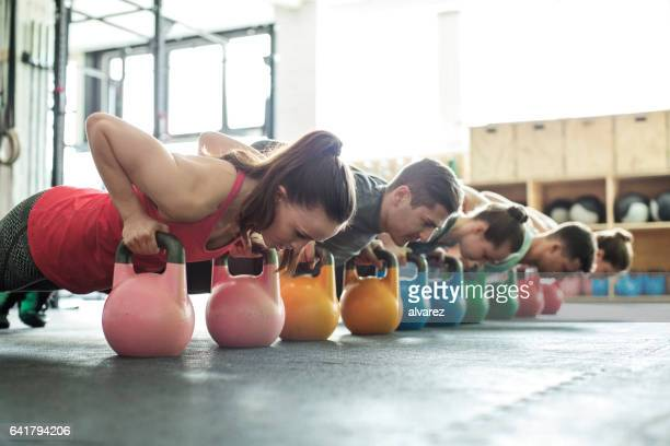 Fitness class doing push-ups with kettle-bells
