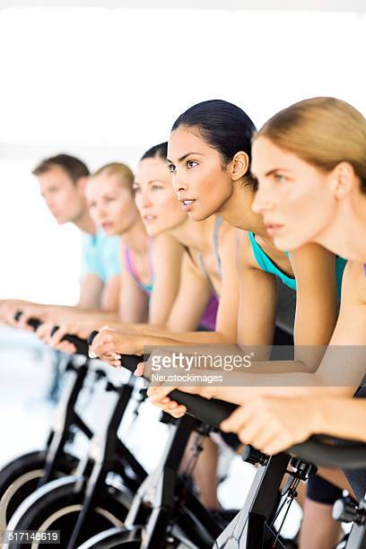 Fitness Class Exercising On Spin Bikes In Health Club