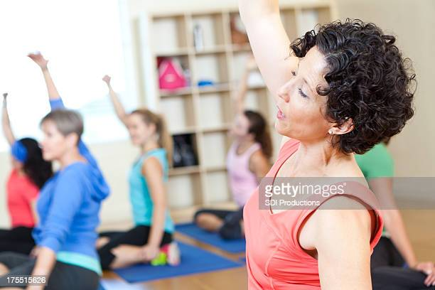 Fitness class of women doing stretching exercises