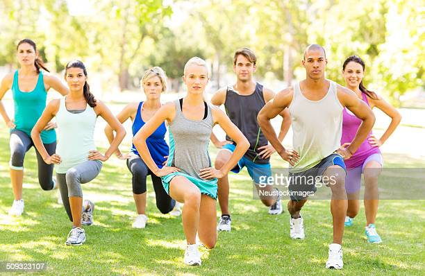 Fitness Class Performing Stretching Exercise In Park