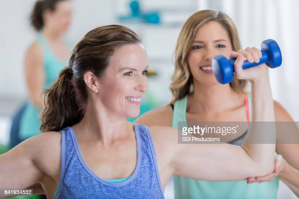 Fitness coach works with client