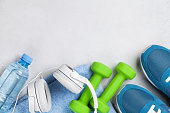 Fitness concept background with sneakers, dumbbells, water bottle and headphones on stone backdrop. Top view with space for your text
