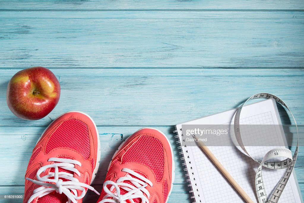 Fitness concept, pink sneakers, apple and notebook and measuring tape : Foto de stock