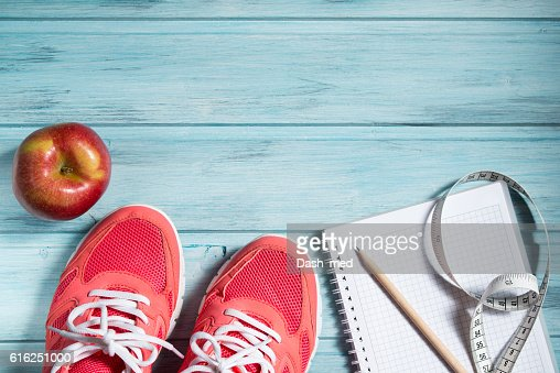 Fitness concept, pink sneakers, apple and notebook and measuring tape : Stock Photo