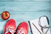 Fitness concept, pink sneakers, red apple and notebook with pencil and measuring tape on wooden background, top view
