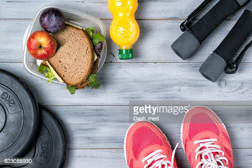 Fitness concept, pink sneakers, weight plates, dumbbells, sandwich : ストックフォト