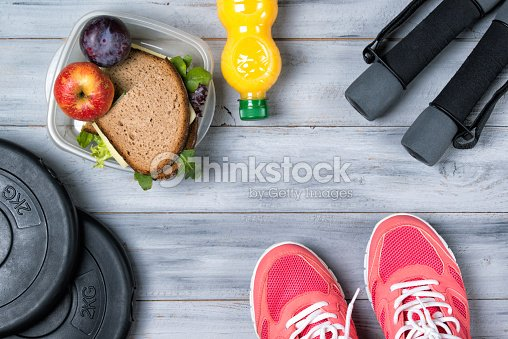Fitness concept, pink sneakers, weight plates, dumbbells, sandwich : Foto de stock
