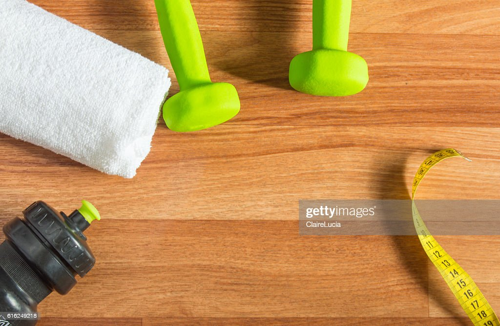 Fitness concept with dumbbells, water bottle, measuring tape, towel on : Foto de stock