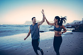 Fitness Couple giving each other high five after hard training session on the beach