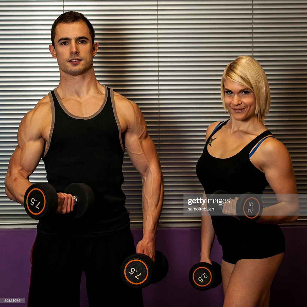 Fitness couple trains in gym with dumbbells : Stock Photo